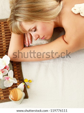 A beautiful woman relaxing in a spa center, isolated on white - stock photo