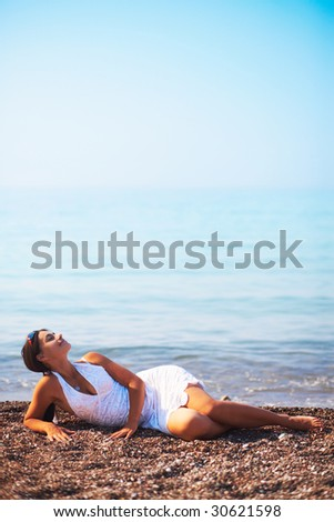 A beautiful woman relaxing on a beach.