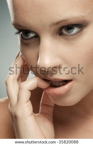 A beautiful woman's face with her finger in her mouth and fingers on her cheeck - stock photo
