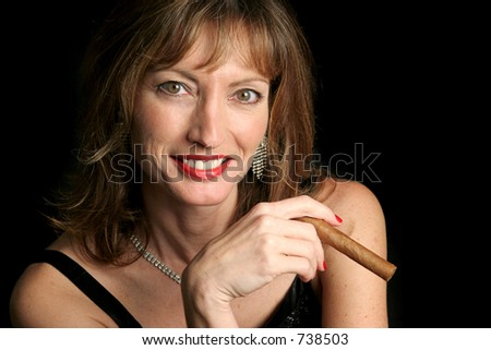 A beautiful woman smiling and holding a cigar against a black background. - stock photo