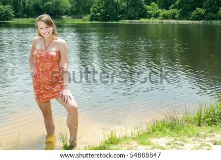 A beautiful woman standing in a lake. - stock photo