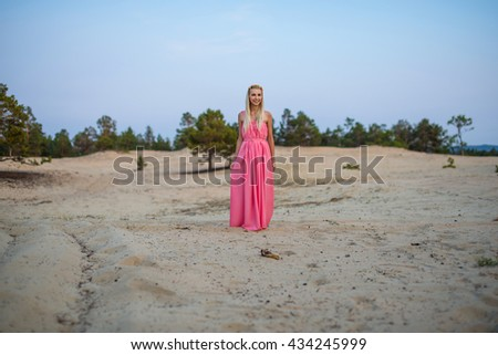 a beautiful woman stands on the sand alone at the background of pine trees, Olkhon island, Baikal - stock photo