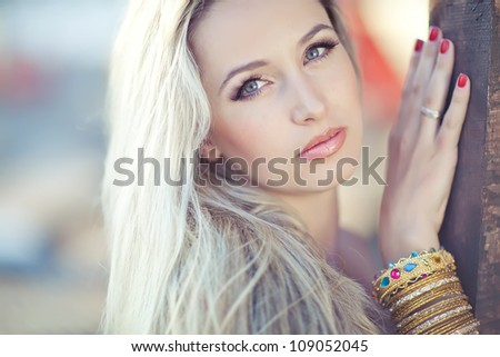 A beautiful woman sunbathing by the pool - stock photo