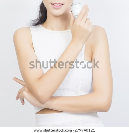 A beautiful woman using a skin care product, moisturizer or lotion - stock photo