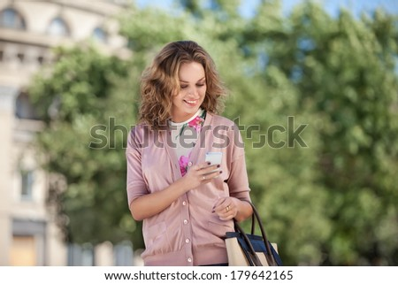 A beautiful woman using wireless internet and checking email via mobile phone in a big city. - stock photo