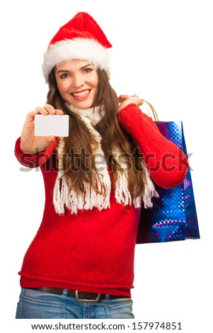 A beautiful woman wearing a Santa hat and holding shopping bags and a blank business card. Isolated on white. - stock photo