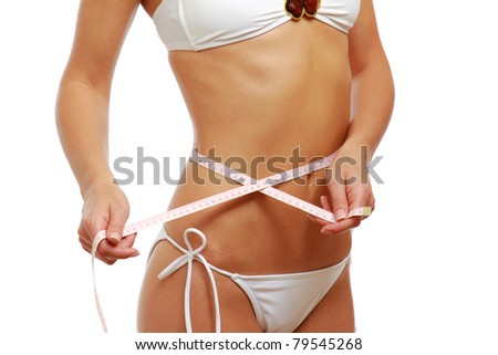 A beautiful woman wearing a swimsuit, measuring her belly, isolated on white - stock photo