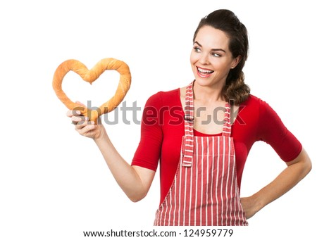 A beautiful woman wearing an apron smiling and holding and looking at a love heart made out of bread. Isolated on white. - stock photo