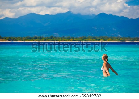 A beautiful woman wearing  white bikini facing the sea on a vacant beach in paradise - stock photo