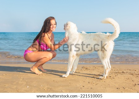 A beautiful woman with a playful young dog on the beach - stock photo