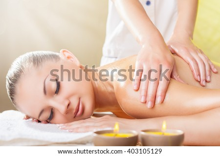 A beautiful woman with her â??â??eyes closed getting a massage at the spa - stock photo