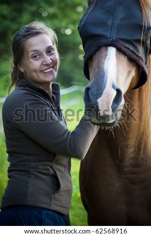 A beautiful woman with her horse at a summer evening, the horse wears a fly mask as protection to stitch fly's - stock photo