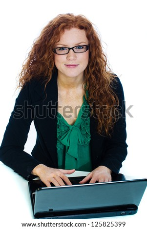 A beautiful woman with naturally curly red hair working on a laptop computer. - stock photo