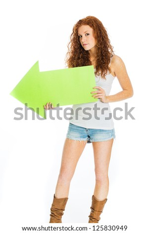 A beautiful woman with red hair holding a green arrow pointing left. - stock photo