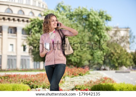 A beautiful woman with the phone holding a cup of take away coffee in a summer city. - stock photo