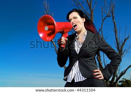 a beautiful woman yelling into a mega phone. - stock photo