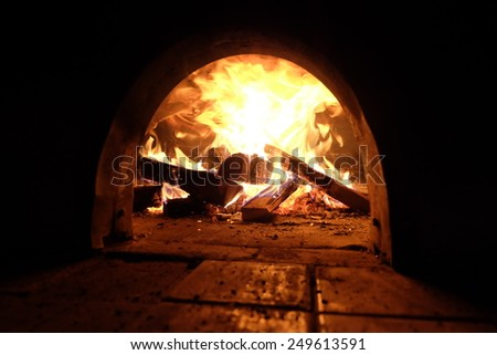 A beautiful wood fired oven with focus on fire. - stock photo