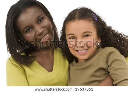 A beautiful young African American mother and her mixed race young daughter having fun - stock photo