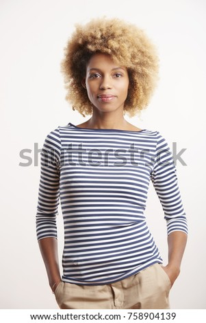 A beautiful young afro-american woman looking at camera and wearing casual clothes while standing against at isolated white background.
