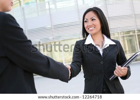 A beautiful young asian business woman shaking hands - stock photo