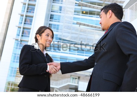 A beautiful young asian business woman shaking hands with man - stock photo