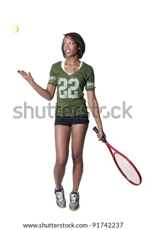 A beautiful young black African American woman playing tennis - stock photo