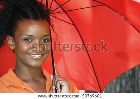A beautiful young black woman holding an umbrella - stock photo