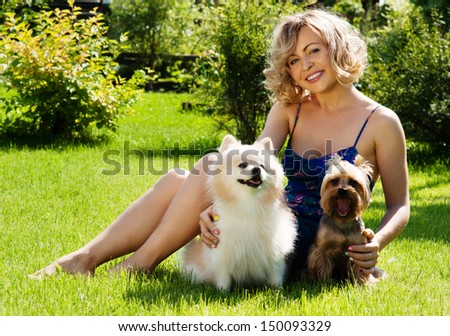 A beautiful young blond girl in the park with dogs - stock photo