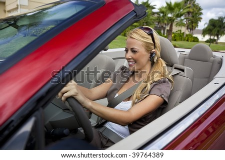 A beautiful young blond woman driving her convertible car and talking on her cell phone with a wireless headset - stock photo