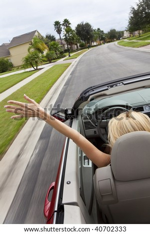 A beautiful young blond woman driving her convertible car with her hand in the air feeling the wind blowing - stock photo