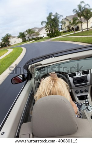 A beautiful young blond woman driving her convertible car with the roof down. - stock photo