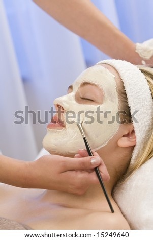 A beautiful young blond woman having a face mask applied by a beautician - stock photo