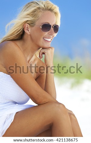 A beautiful young blond woman smiling in aviator sunglasses and a white sundress sitting on a deserted tropical beach