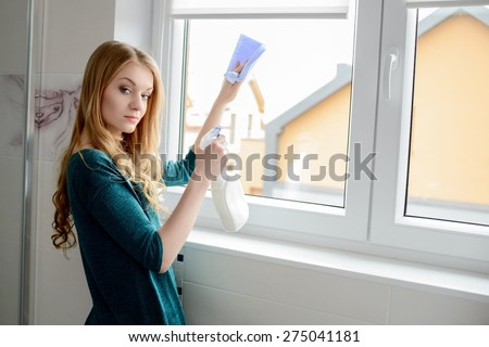 A beautiful young blond woman washes a window in the bathroom - stock photo