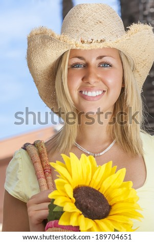 A beautiful young blond woman wearing a straw cowboy hat and smiling while carrying a shopping bag of sunflowers  - stock photo