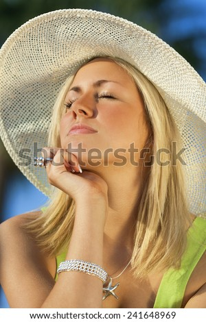 A beautiful young blond woman wearing a sun hat eyes closed enjoyed getting a sun tan on her face - stock photo