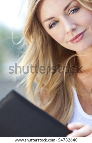 A beautiful young blond woman with stunning blue eyes reading a folder or menu - stock photo