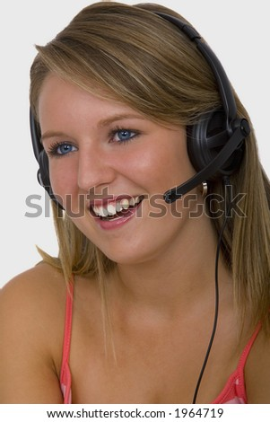 A beautiful young blonde telephonist smiling and speaking on a headset