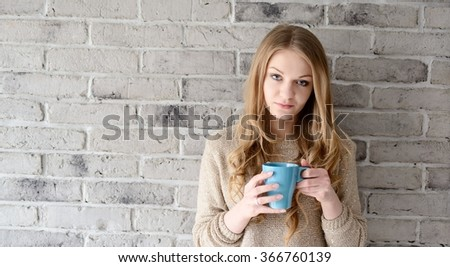 A beautiful young blonde woman drinking coffee from a cup. She stands near a brick wall - stock photo