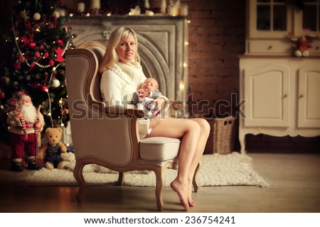 A beautiful young blonde woman in white clothes sitting in a chair and holding her cute newborn baby on her knees against a decorated twinkling Christmas tree. New Year's Eve. - stock photo