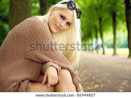 A beautiful young blonde woman sits in a park enjoying the quiet beauty of her surroundings, beauty in nature and humans. - stock photo