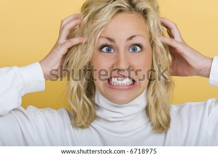 A beautiful young blue eyed blond woman getting very frustrated - stock photo