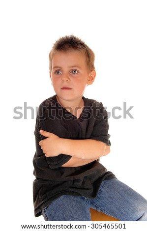 A beautiful young boy sitting on a chair in a black t-shirt, hugginghimself, isolated for white background. - stock photo