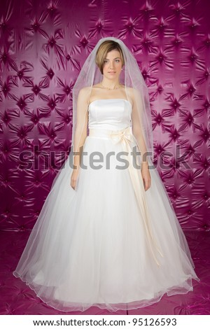 a beautiful young bride in a pink studio - stock photo
