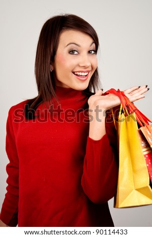 A beautiful young brunette girl smiling happily. Bee hand bags with Christmas and New Year shopping. - stock photo