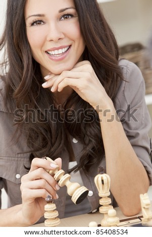 A beautiful young brunette Latina woman with a wonderful toothy smile playing chess at home - stock photo