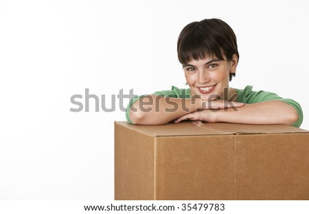 A beautiful young brunette posing while resting her arms on a cardboard box.  She is smiling directly at the camera. Horizontally framed shot. - stock photo