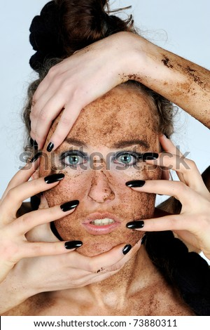 A beautiful young brunette woman having a mud face mask - stock photo
