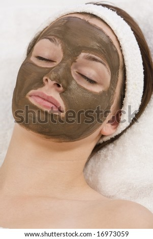 A beautiful young brunette woman rests after having a chocolate face mask applied by a beautician - stock photo