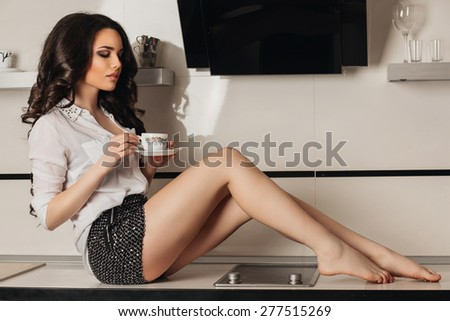a beautiful young brunette woman with long hair and long legs with a cup - stock photo